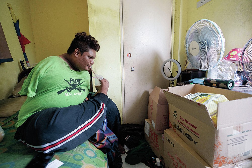 Mohamad Nor Abdullah, born without arms, drinks near donated goods in his rented room in Kuala Lumpur, Malaysia on July 3, 2021. When Mohamad Nor put a white flag outside his window late at night, he didn't expect the swift outpouring of support. By morning, dozens of strangers knocked on his door, offering food, cash and encouragement. (AP Photo/Vincent Thian)