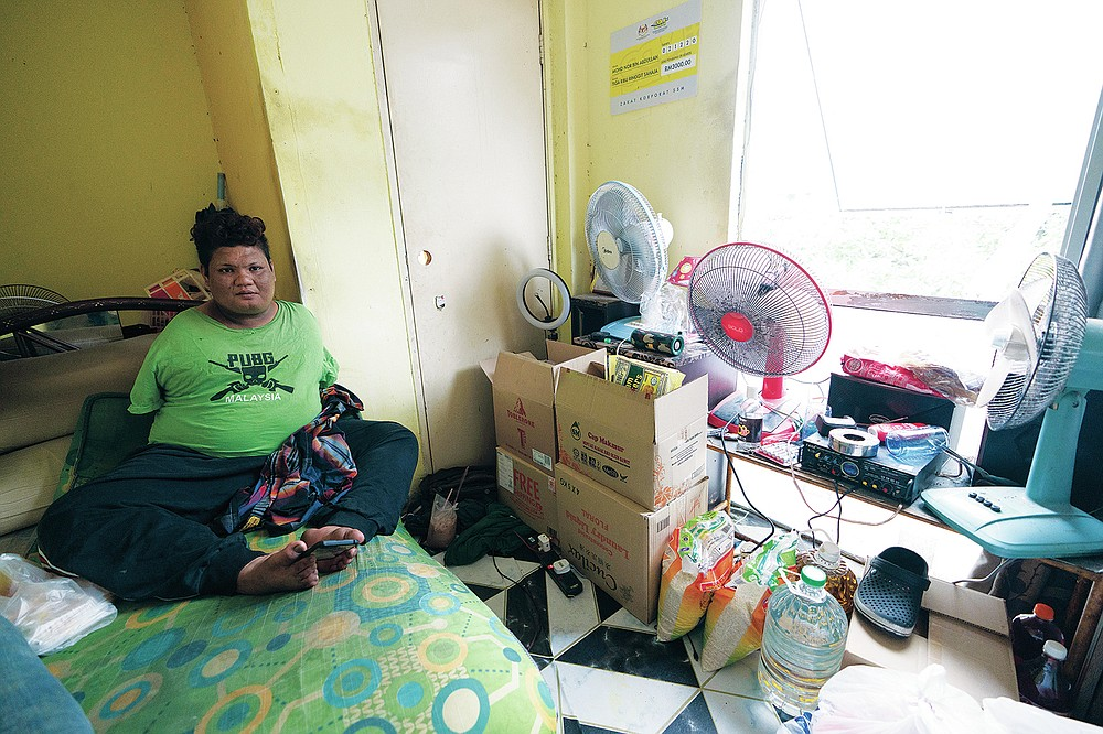Mohamad Nor Abdullah, born without arms, sits near donated goods, right, in his rented room in Kuala Lumpur, Malaysia on July 3, 2021. When Mohamad Nor put a white flag outside his window late at night, he didn't expect the swift outpouring of support. By morning, dozens of strangers knocked on his door, offering food, cash and encouragement. (AP Photo/Vincent Thian)