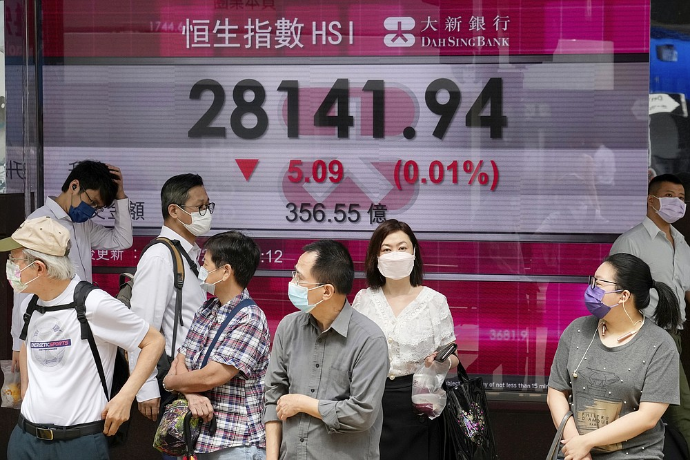 People wearing face masks walk past a bank's electronic board showing the Hong Kong share index in Hong Kong, Tuesday, July 6, 2021. Asian shares were mixed in muted trading on Tuesday as oil prices surged higher after a meeting of oil producing nations was postponed. (AP Photo/Kin Cheung)