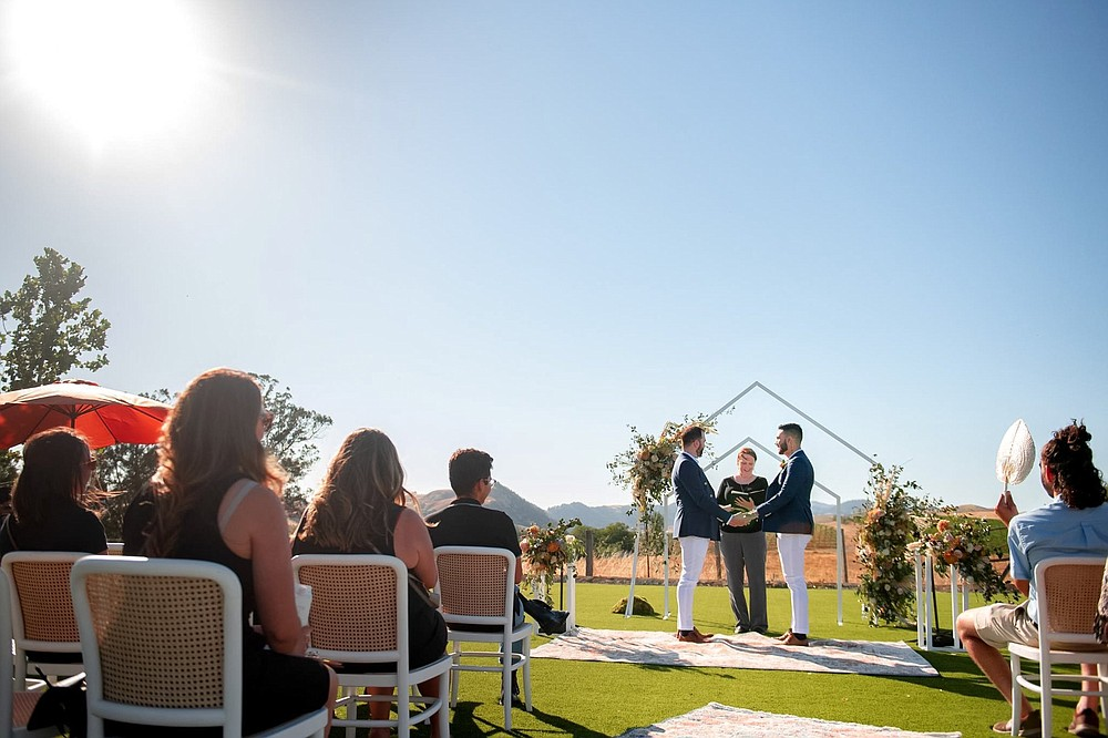 With roling hills in the distance, Michael DeSalvo Solarte (left) and Alejandro Solarte DeSalvo exchange vows June 25, 2021, at Carneros Resort and Spa in the Napa Valley region of California. The couple won a contest sponsored by Visit California to have their wedding at the resort. (Special to the Democrat-Gazette/Max Whittaker)