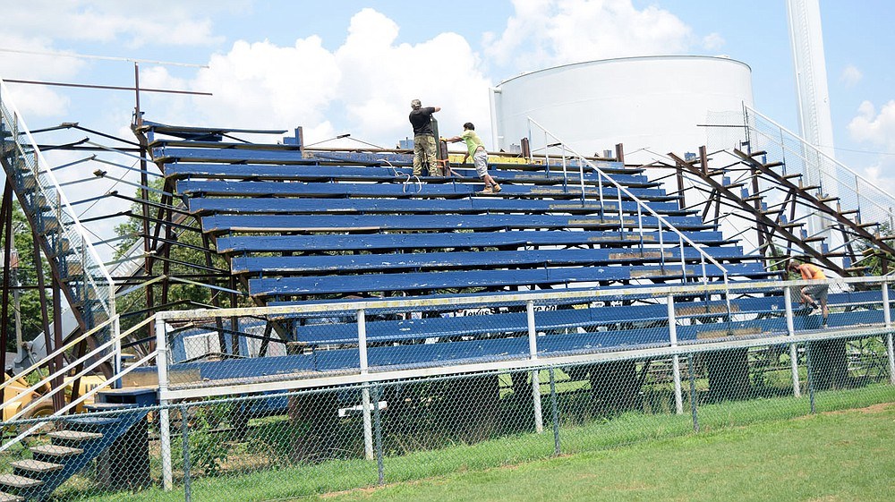 Westside Eagle Observer/MIKE ECKELS After removing the press box and two end sections of bleachers at Bulldog Stadium in Decatur July 7, workers turn their attention to the wood seats at the top. By Friday afternoon, the long standing Decatur landmark was taken down and transported off site.