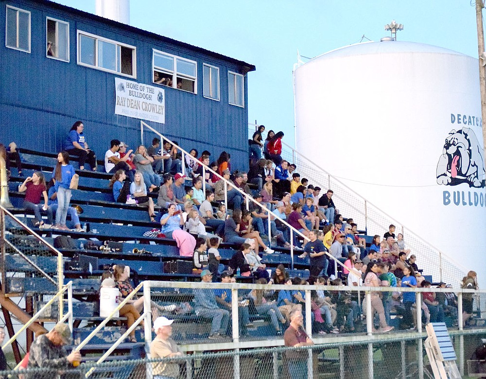 Westside Eagle Observer/MIKE ECKELS  The bleachers at Bulldog Stadium in Decatur were filled with middle and high school band members and fans during the open game of the eight-man football season August 30, 2019. This Decatur landmark was disassembled July 9 to make way for a new set of aluminum bleachers.