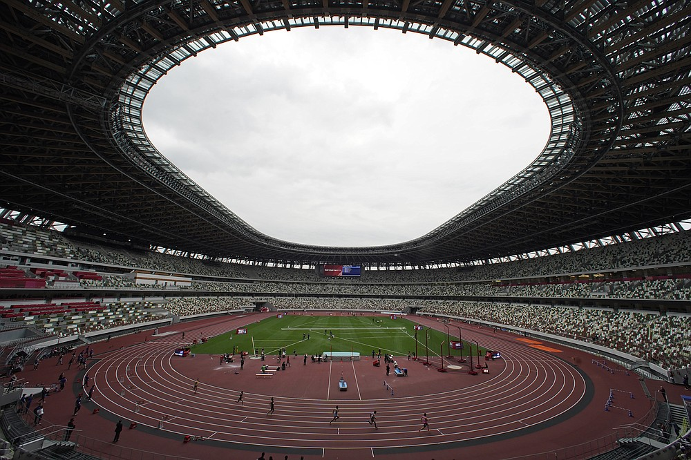 In this May 11, 2021, file photo, athletes compete in the men's 400-meter T20 race during an athletics test event for the Tokyo 2020 Paralympics Games at National Stadium in Tokyo. The pandemic-delayed Tokyo Olympics are shaping up as a TV-only event with few fans — if any — being allowed when they open in just over two weeks. Japan's Asahi newspaper, citing multiple unidentified government sources, says the opening ceremony will be limited only to VIP guests. (AP Photo/Shuji Kajiyama, File)