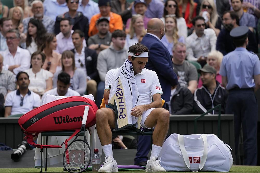 Szwajcar Roger Federer ociera twarz ręcznikiem podczas meczu ćwierćfinałowego singla mężczyzn z Polakiem Hubertem Hurkaczem dziewiątego dnia Wimbledonu w Londynie, 7 lipca 2021 r.  (Zdjęcie AP / Kirsty Wigglesworth)
