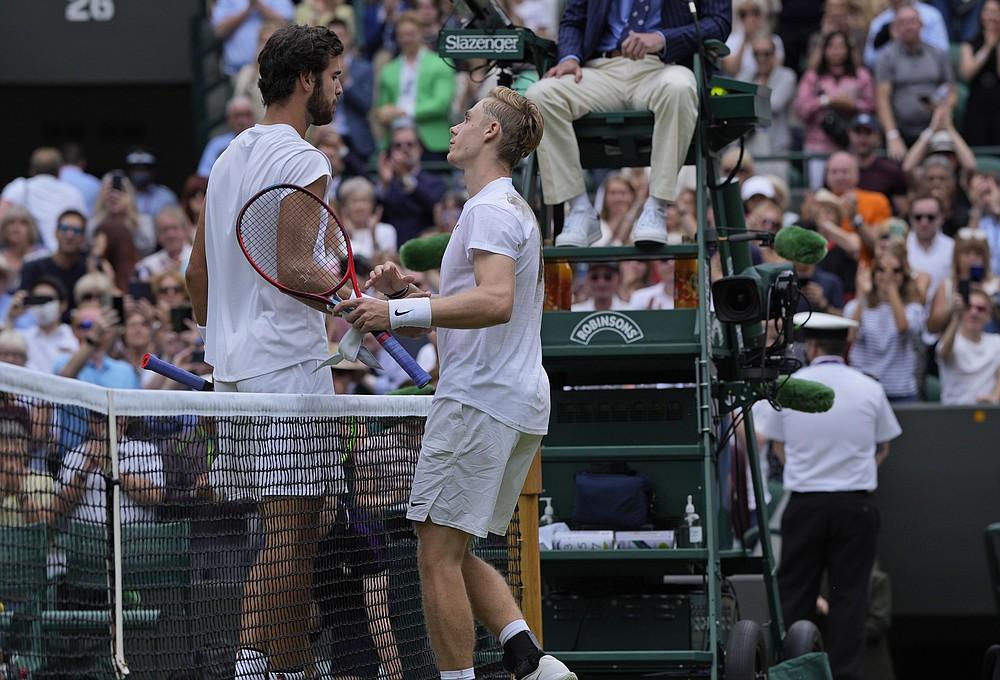 Kanadyjczyk Denis Shapovalov, po prawej, wita Rosjankę Karen Khachanov pod koniec meczu ćwierćfinałowego w grze pojedynczej mężczyzn w dziewiątym dniu Wimbledonu Tennis Championships w Londynie, 7 lipca 2021 r. (AP Photo / Alastair Grant)