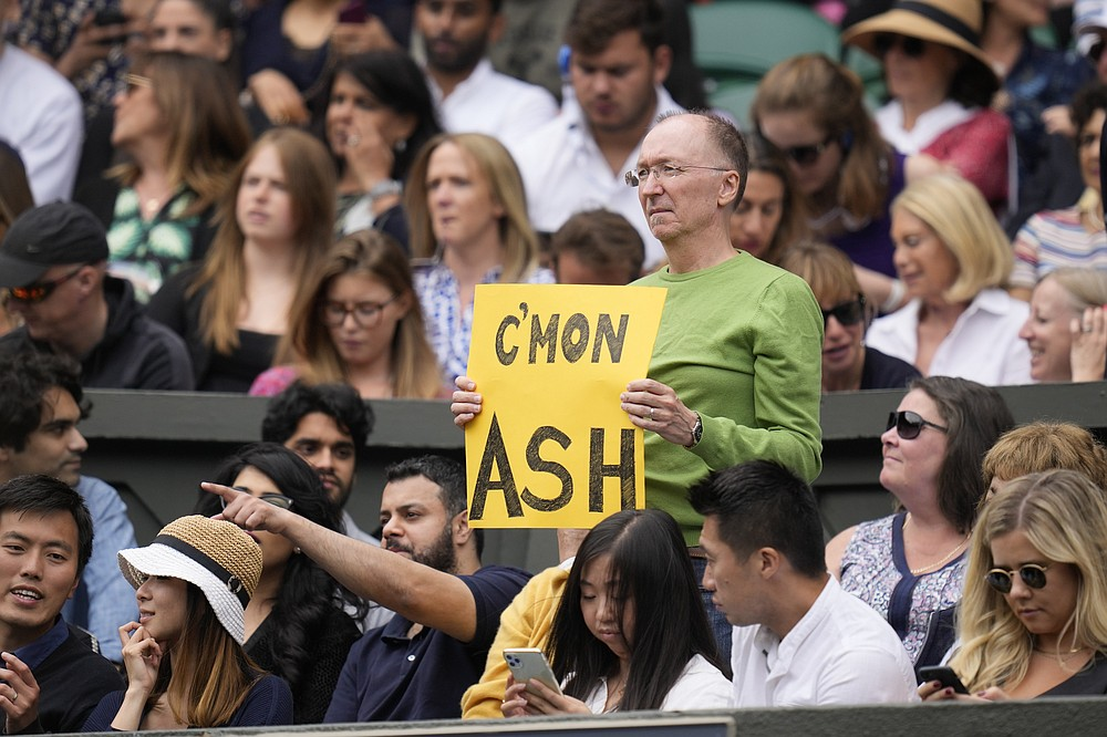 Ein Zuschauer hält ein Banner zur Unterstützung der Australierin Ashleigh Barty während des Halbfinalspiels im Dameneinzel gegen die Deutsche Angelique Kerber am 10. Tag der Wimbledon Tennis Championships in London, Donnerstag, 8. Juli 2021 (AP Photo/Kirsty Wigglesworth)
