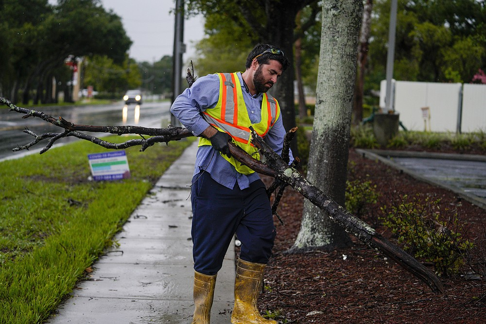 Michael Ciarleglio with the city of Pinellas Park, cleans up a few tree branches while working the morning after Hurricane Elsa moved over the Tampa Bay Area, Wednesday, July 7, 2021 in Pinellas Park, Fla. The Tampa Bay area was spared major damage as Elsa stayed off shore as it passed by.  (Martha Asencio-Rhine/Tampa Bay Times via AP)
