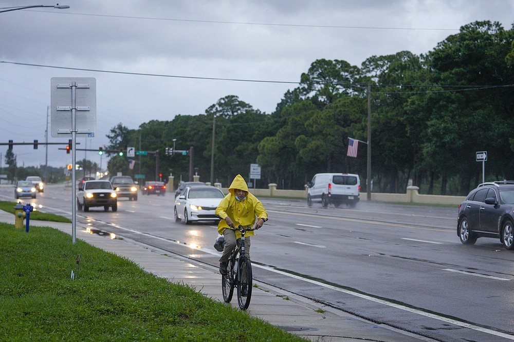 A cyclist makes his way long Bay Pines Boulevard the morning after Hurricane Elsa moved over the Tampa Bay Area, Wednesday, July 7, 2021 in St. Petersburg, Fla. (Martha Asencio-Rhine/Tampa Bay Times via AP)