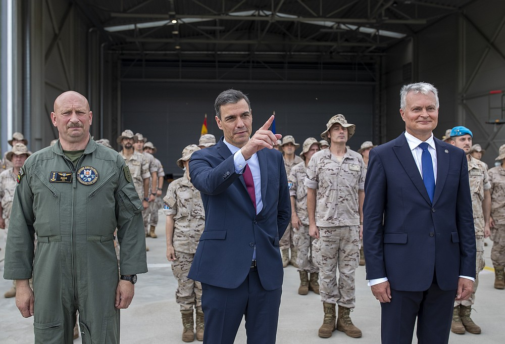 Commander of the Lithuanian Air Force Col. Dainius Guzas, left, Lithuania's President Gitanas Nauseda, right, and Spain's Prime Minister Pedro Sanchez pose for photographers during a visit to the military air force base at Siauliai, some 220 kms (136,7 miles) east of the capital Vilnius, Lithuania, Thursday, July 8, 2021. (AP Photo/Mindaugas Kulbis)