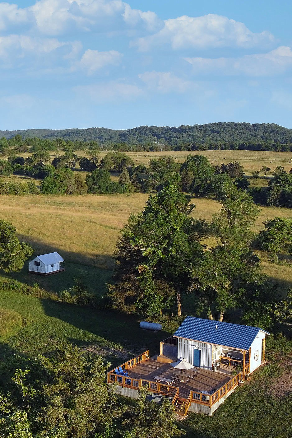 PHOTO COURTESY OF SUNSHINE JOY/The views from atop the hill at Little Sugar Farm are crowd-pleasers. From the outdoor kitchen and patio (right) you can see Little Sugar Creek while views from a safari tent (left) look over rolling hills and greenery.