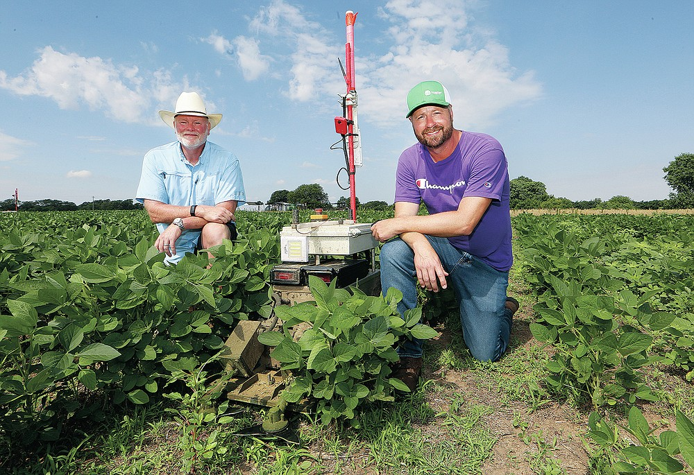 Greenfield Robotics is a company that builds robots who control weeds by cutting them down without tillage and without herbicides, owned by Kansas farmer Clint Brauer, right, with Jerry Poole, President, left, on Tuesday, July 6, 2021, in a field near Cheney, Kan. (Sandra J. Milburn/The Hutchinson News via AP)