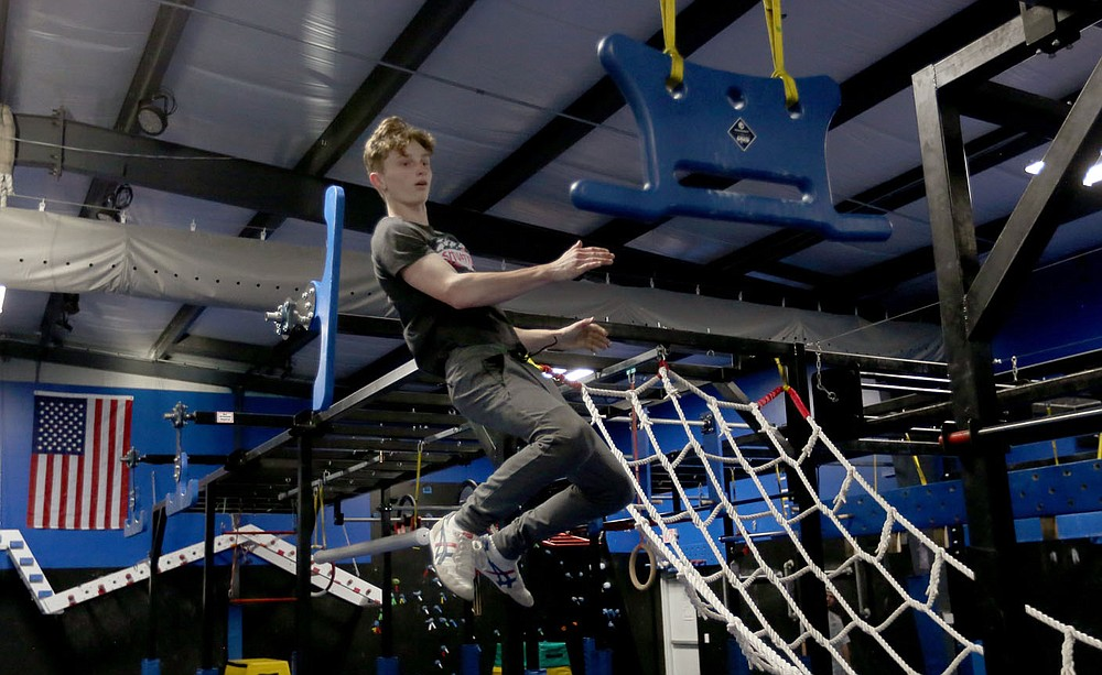 Bentonville West High School student Owen Dyer, 16, a competitor in the new Ninja Warrior's teen category flies between hand holds on an obstacle as he trains Tuesday, July 6, 2021, at Flip Side Ninja Park Lowell. Check out nwaonline.com/210711Daily/ and nwadg.com/photos for a photo gallery.(NWA Democrat-Gazette/David Gottschalk)