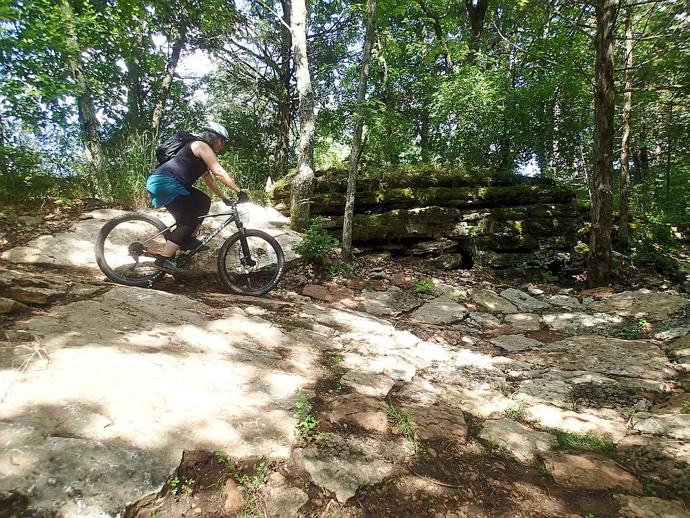 Suzanne Schmidt heads into a tight, rocky turn June 11 2021 on the Marble Flats trails.  (NWA Democrat-Gazette/Flip Putthoff)