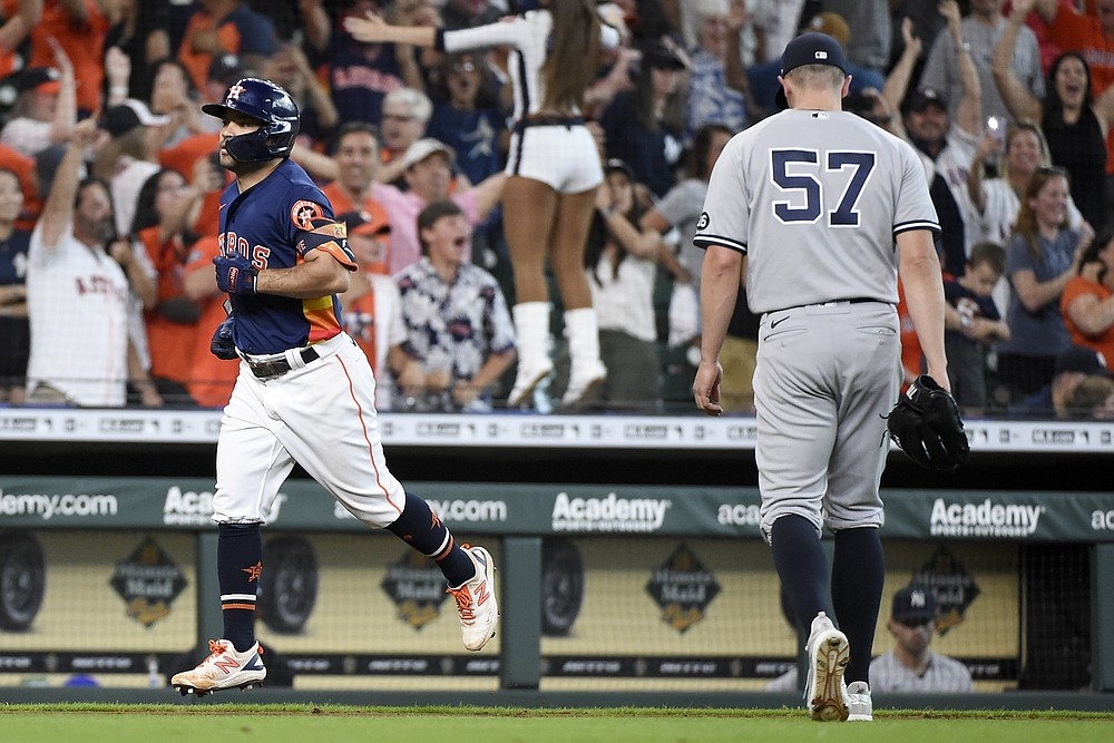 Houston Astros' Jose Altuve, left, rounds the bases after hitting a winning three-run home run as New York Yankees relief pitcher Chad Green (57) walks off the field during the ninth inning of a baseball game Sunday, July 11, 2021, in Houston. (AP Photo/Eric Christian Smith)