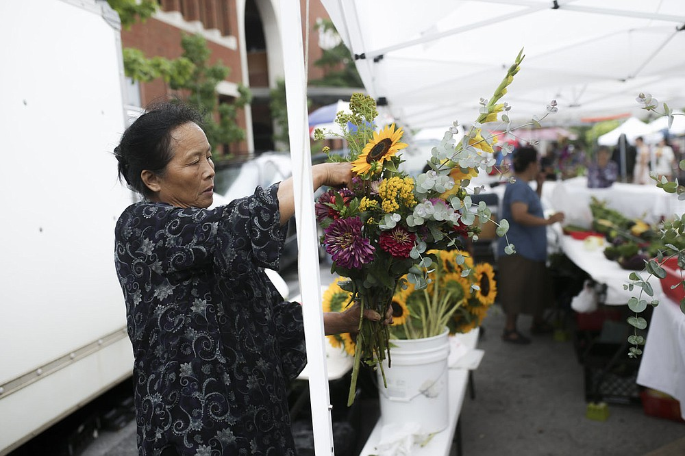 Vab Yang of Siloam Springs arranges flowers at her booth Lee Produce, Saturday, July 10, 2021 during the farmer's market at the downtown square in Fayetteville. Check out nwaonline.com/210711Daily/ for today's photo gallery.  (NWA Democrat-Gazette/Charlie Kaijo)