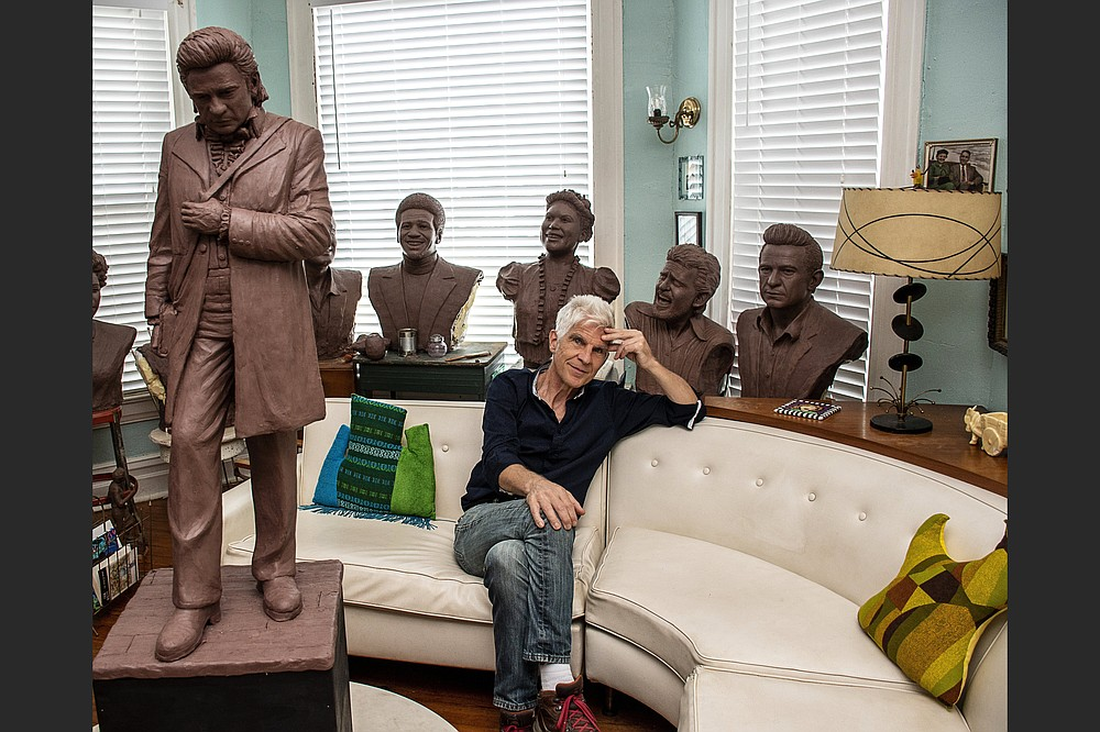 Artist Kevin Kresse sits among clay models he created of Arkansas singing legends — including Johnny Cash, whose statue, created by Kresse and cast in bronze, will be placed in the U.S. Capitol. (Arkansas Democrat-Gazette/Cary Jenkins)