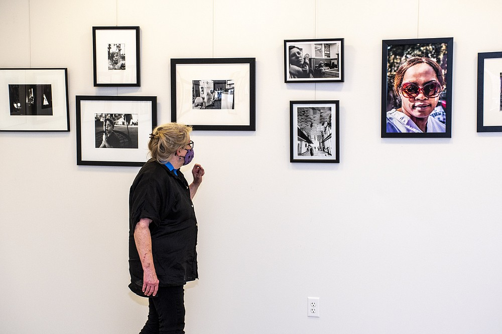 """Rita Henry of the Blue-Eyed Knocker Photo Club inspects photos that are part of """"Humankind,"""" a photography exhibit Friday-Sept. 10 at the Argenta Branch Library in North Little Rock. (Arkansas Democrat-Gazette/Cary Jenkins)"""