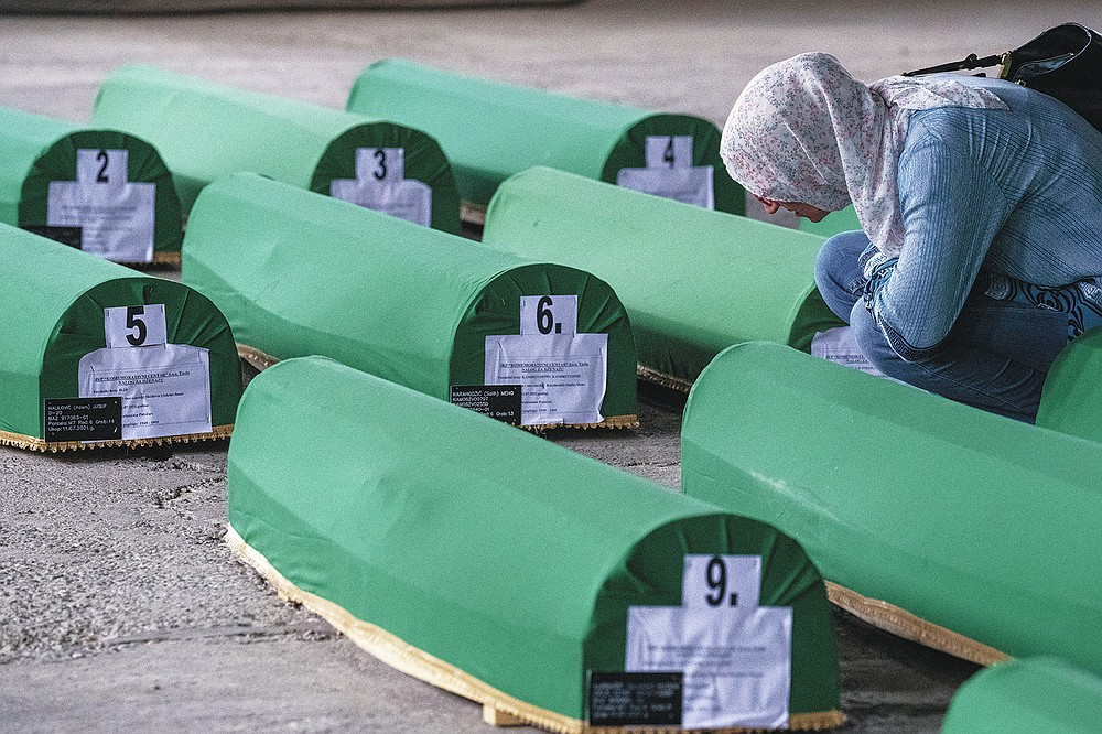 A woman inspect caskets of 19 identified victims which will be buried in Srebrenica on Sunday, in Potocari, Bosnia, Saturday, July 10, 2021. Bosnia commemorates more than 8,000 Bosnian Muslims men and boys who perished 26 years ago during 10 days of slaughter after Srebrenica was overrun by Bosnian Serb forces on July 11, 1995, during Bosnia's 1992-95 war. (AP Photo/Darko Bandic)