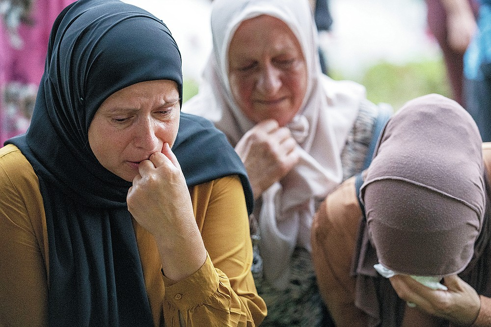 Women mourn next to bodies of 19 identified victims which will be buried in Srebrenica on Sunday, in Potocari, Bosnia, Saturday, July 10, 2021. Bosnia commemorates more than 8,000 Bosnian Muslims men and boys who perished 26 years ago during 10 days of slaughter after Srebrenica was overrun by Bosnian Serb forces on July 11, 1995, during Bosnia's 1992-95 war. (AP Photo/Darko Bandic)