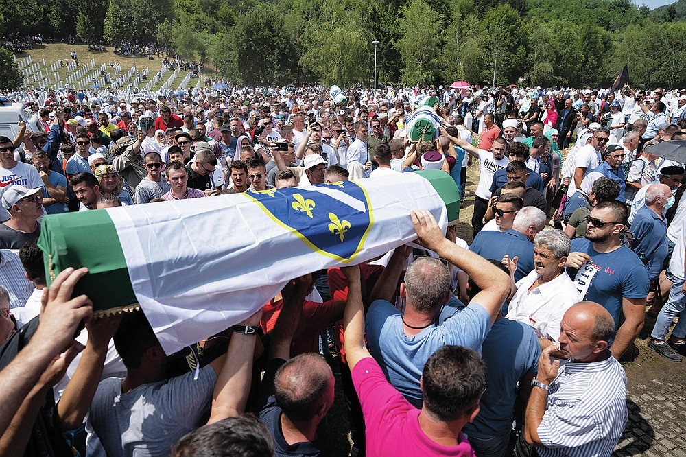 Mourners carry caskets of newly identified victims during their funeral at the memorial cemetery in Potocari near Srebrenica, Bosnia, Sunday, July 11, 2021. Bosnia is marking the 26th anniversary of the Srebrenica massacre, the only episode of its 1992-95 fratricidal war that has been declared a genocide by international and national courts. The brutal execution of more than 8,000 Muslim Bosniaks by Bosnian Serb troops is being commemorated by a series of events Sunday. (AP Photo/Darko Bandic)