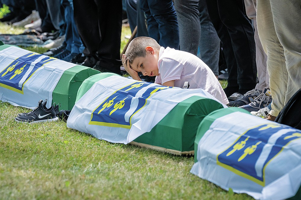 A boy reacts as mourners prepare for the funeral of newly identified victims at the memorial cemetery in Potocari near Srebrenica, Bosnia, Sunday, July 11, 2021. Bosnia is marking the 26th anniversary of the Srebrenica massacre, the only episode of its 1992-95 fratricidal war that has been declared a genocide by international and national courts. The brutal execution of more than 8,000 Muslim Bosniaks by Bosnian Serb troops is being commemorated by a series of events Sunday. (AP Photo/Darko Bandic)