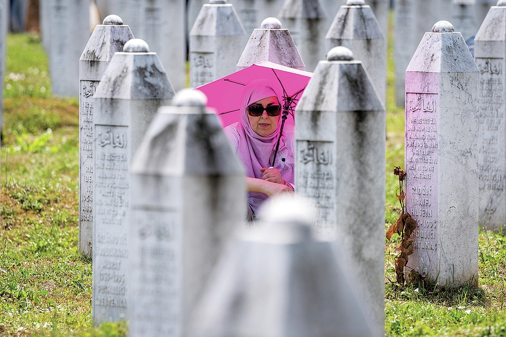A woman visits the memorial cemetery in Potocari near Srebrenica, Bosnia, Sunday, July 11, 2021. Bosnia is marking the 26th anniversary of the Srebrenica massacre, the only episode of its 1992-95 fratricidal war that has been declared a genocide by international and national courts. The brutal execution of more than 8,000 Muslim Bosniaks by Bosnian Serb troops is being commemorated by a series of events Sunday. (AP Photo/Darko Bandic)
