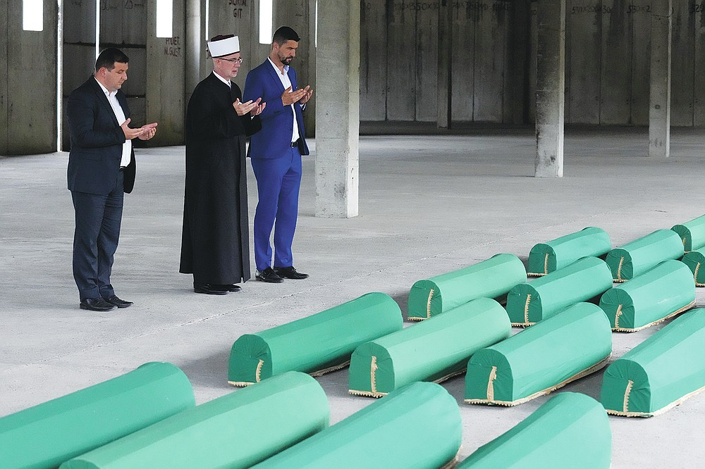 A muslim cleric and two other men pay respect next to the caskets of 19 identified victims which will be buried in Srebrenica on Sunday, in Potocari, Bosnia, Saturday, July 10, 2021. Bosnia commemorates more than 8,000 Bosnian Muslims men and boys who perished 26 years ago during 10 days of slaughter after Srebrenica was overrun by Bosnian Serb forces on July 11, 1995, during Bosnia's 1992-95 war. (AP Photo/Darko Bandic)