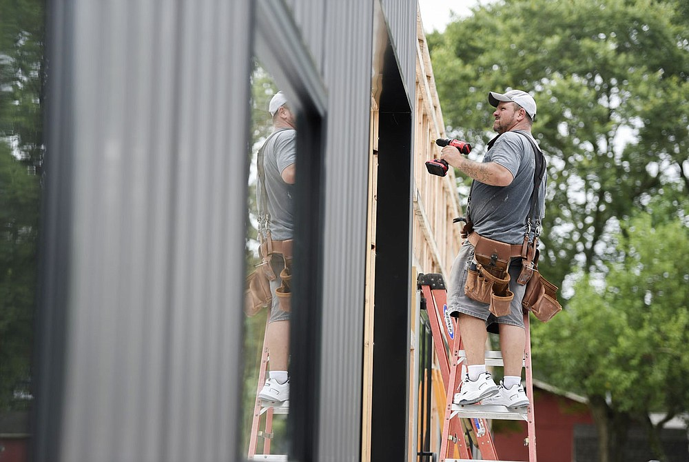 Dave Evans of Bentonville screws metal sheeting to the frame of a building, Monday, July 12, 2021 at a private property along Springvalley Rd. in Bentonville. Raymond Barett is building properties to lease out to private businesses as an income source. Check out nwaonline.com/210713Daily/ for today's photo gallery.  (NWA Democrat-Gazette/Charlie Kaijo)