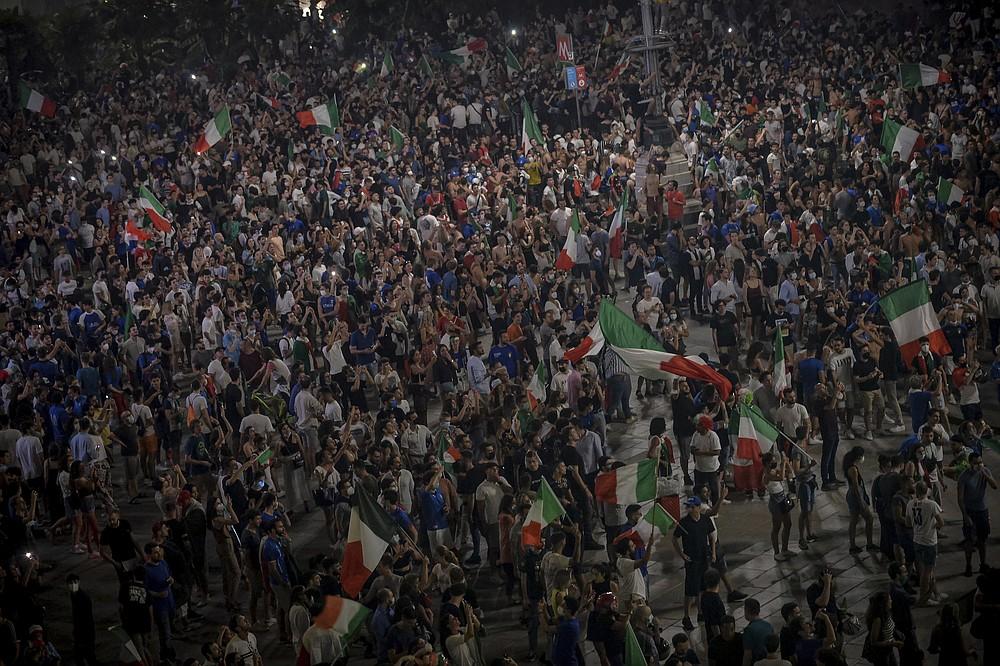 I fan festeggiano al Duomo di Milano, in Italia, domenica 11 luglio 2021, dopo che la loro squadra ha vinto l'Europeo contro l'Inghilterra.  L'Italia ha vinto per la seconda volta l'Europeo battendo domenica l'Inghilterra 3-2 ai rigori.  (Claudio Forlan/La Presse via The Associated Press)