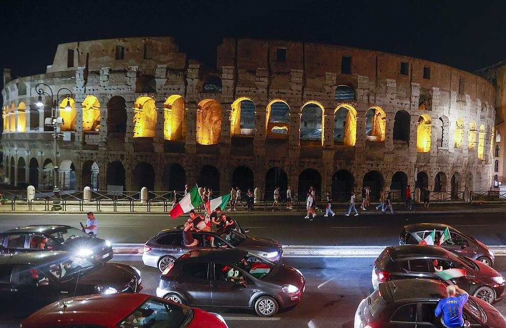 I tifosi italiani festeggiano davanti all'antico Colosseo a Roma, lunedì 12 luglio 2021, dopo che l'Italia ha battuto l'Inghilterra per vincere il Campionato europeo di calcio 2020 nella partita finale tenutasi allo stadio di Wembley a Londra.  L'Italia ha battuto l'Inghilterra 3-2 ai rigori dopo l'1-1.  (Foto AP/Riccardo De Luca)