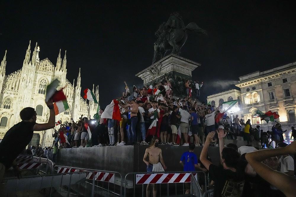 I tifosi italiani festeggiano davanti al Duomo di Milano, lunedì 12 luglio 2021, dopo che l'Italia ha battuto l'Inghilterra per vincere gli Europei di calcio 2020 nella partita finale disputata allo stadio di Wembley a Londra.  L'Italia ha battuto l'Inghilterra 3-2 ai rigori dopo l'1-1.  (Foto AP/Luca Bruno)