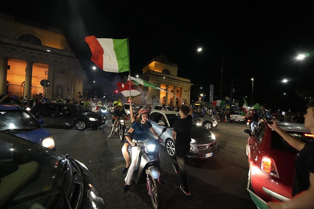 I tifosi italiani festeggiano a Milano, in Italia, lunedì 12 luglio 2021, dopo che l'Italia ha battuto l'Inghilterra per vincere il Campionato europeo di calcio 2020 nella partita finale tenutasi allo stadio di Wembley a Londra.  L'Italia ha battuto l'Inghilterra 3-2 ai rigori dopo l'1-1.  (Foto AP/Luca Bruno)