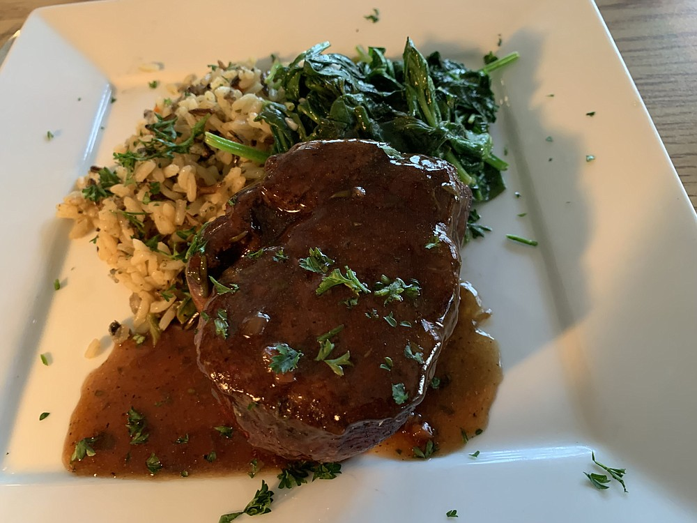 Wednesday is Special Cheap Steak Night at Walter's Green Room; this $32 ribeye, topped with a bourbon demi-glace (with spinach and wild rice) was $25. (Arkansas Democrat-Gazette/Eric E. Harrison)