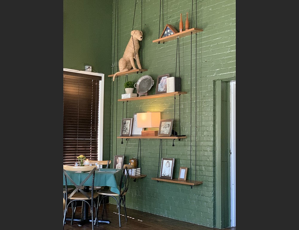 """The walls, tablecloths and napkins are green at Walter's Green Room; several decor items, including a wicker-work dog and """"relics"""" from a former restaurant appear on shelves near the front of the restaurant. (Arkansas Democrat-Gazette/Eric E. Harrison)"""