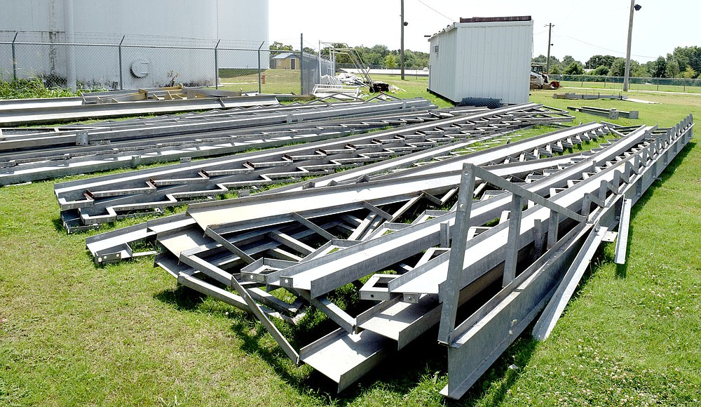 Westside Eagle Observer/MIKE ECKELS A metal jigsaw puzzle of seat supports occupies the ground near the old bleachers at Bulldog Stadium in Decatur July 14. Once these pieces are put together, they will form the new bleachers at Bulldog Stadium which will have nearly double the capacity of the old wooden structure.