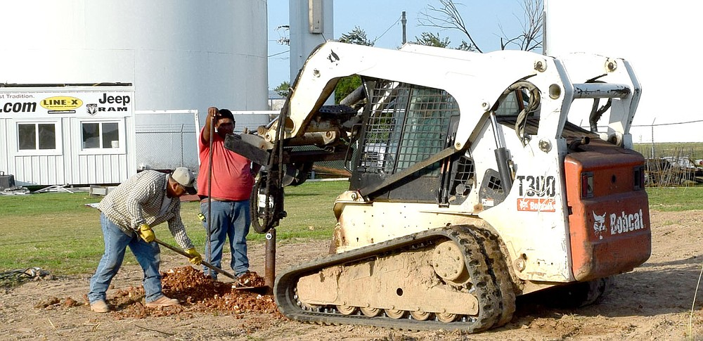 Westside Eagle Observer/MIKE ECKELS Workers clear away dirt as a hydraulic drill attached to a Bobcat skid loader digs holes for the footing for the new bleachers at Bulldog Stadium in Decatur July 14.
