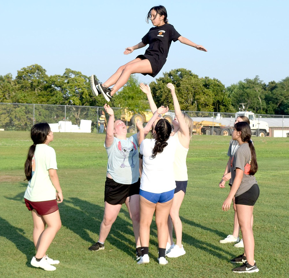 Westside Eagle Observer/MIKE ECKELS McKenzie Thao (top) does a dismount from a prep stunt during the July 13 Decatur cheer team practice at Bulldog Stadium in Decatur. At present, the cheer team, volleyball and boys and girls basketball are all preparing for the 2021-22 sports season.