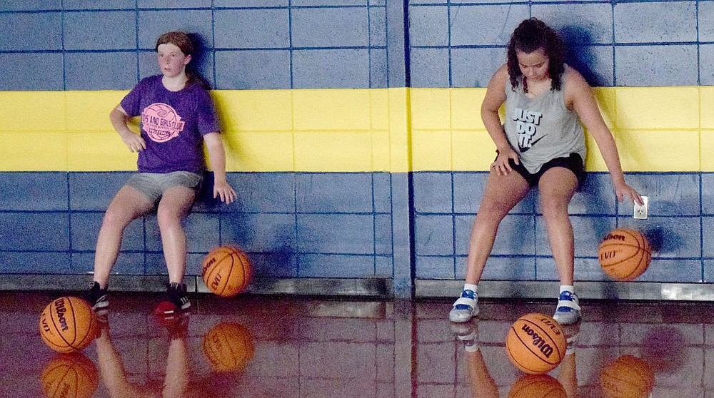 Westside Eagle Observer/MIKE ECKELS Sydnie Brooks (left) and Ariana Kumbera work on their dribbling skills during the Lady Bulldog junior high basketball practice at Peterson Gym in Decatur July 14.
