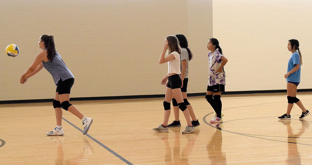 Westside Eagle Observer/MIKE ECKELS Ariana Kumbera (left) leads four other Lady Bulldog junior high volleyball players in an exercise in which the girls hit the ball to teammates on the opposite side of the court during junior high volleyball practice at Decatur Middle School Gym Thursday morning. The exercise is designed to teach the players to control their hits as they return the ball back and forth over the net.