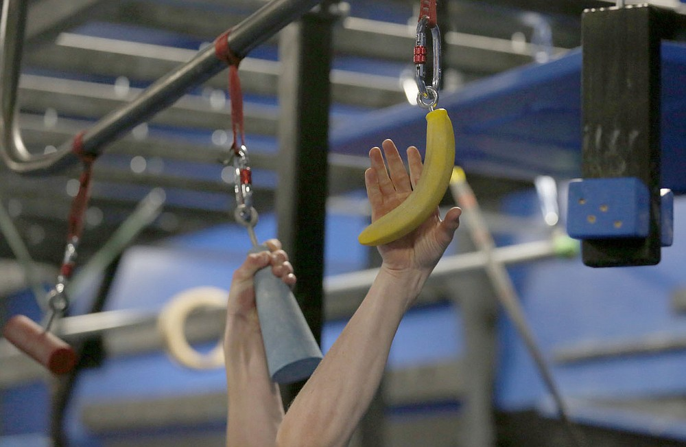 Bentonville West High School student Owen Dyer, 16, a competitor in the new Ninja Warrior's teen category reaches for a banana shaped hold as he trains Tuesday, July 6, 2021, at Flip Side Ninja Park Lowell. Check out nwaonline.com/210711Daily/ and nwadg.com/photos for a photo gallery.(NWA Democrat-Gazette/David Gottschalk)