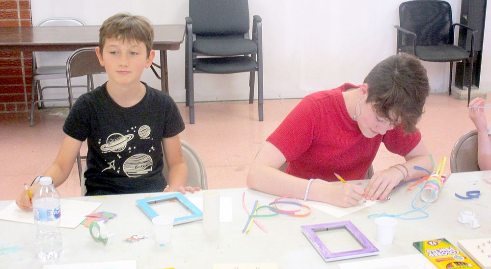 Marc Hayot/Herald-Leader Brian Thompson (left), takes a break from his project while Emery Case works diligently on hers. Thompson and Case were one of two kids who participated in the senior art program held by the Parks and Recreation division the week of the July 12.