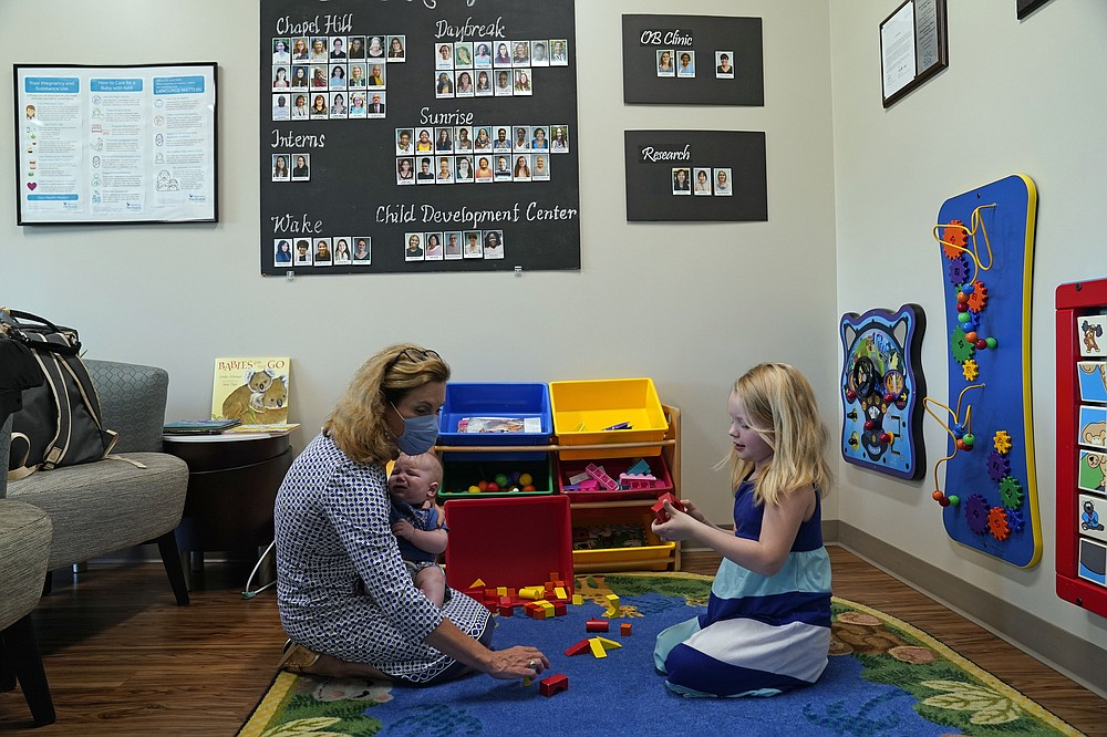 Hendrée Jones, executive director of Horizons, plays with patient Megan Sims' children in Carrboro, N.C., Tuesday, July 13, 2021. Horizons, a substance use disorder treatment program at the University of North Carolina's School of Medicine is designed specifically for pregnant women and mothers. (AP Photo/Gerry Broome)