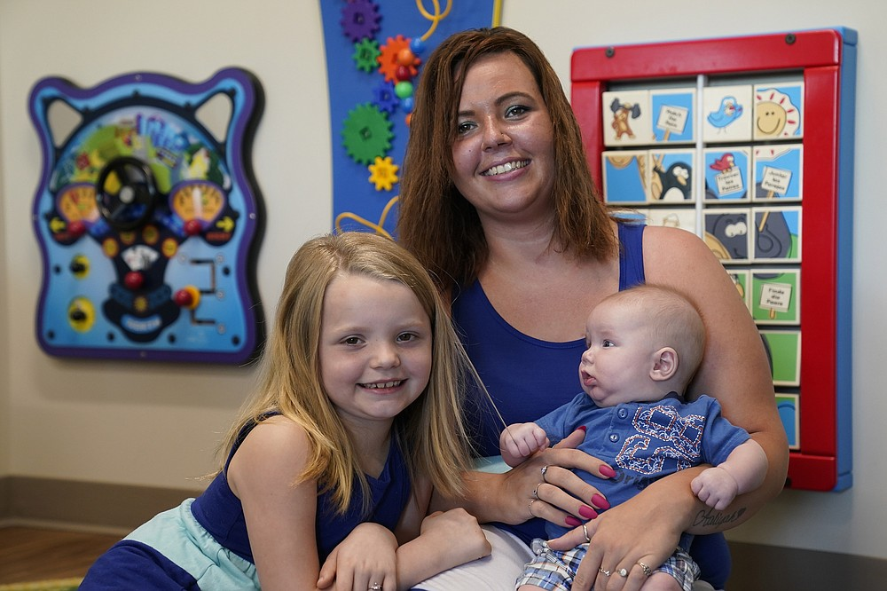 """Megan Sims is shown with her children, 3 month-old Christian and Aaliyah, 7, in Carrboro, N.C., Tuesday, July 13, 2021. Sims couldn't stop using drugs during the pandemic, even as she discovered she was pregnant. Through word of mouth, Sims discovered Horizons, a substance use disorder treatment program at the University of North Carolina's School of Medicine that is designed specifically for pregnant women and mothers. """"Horizons saved my life."""" Sims said. (AP Photo/Gerry Broome)"""