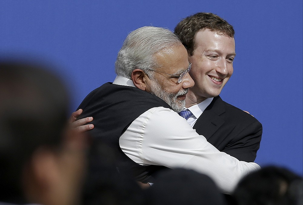 FILE - In this September 27, 2015 file photo, Facebook CEO Mark Zuckerberg, right, kisses Indian Prime Minister Narendra Modi on Facebook in Menlo Park, Calif.  like Twitter and Facebook under direct government surveillance are needed to crack down on disinformation and hate speech and to give users more power to report objectionable content.  Critics of the law fear it could lead to outright censorship in a country where digital freedoms have been shrinking since Modi took office in 2014, with many calling him