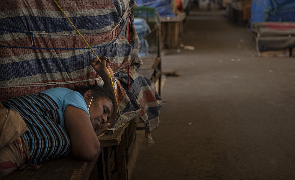 A Sri Lankan vegetable vendor sleeps by her stall at a wholesale vegetable market closed to curb the spread of the coronavirus in Colombo, Sri Lanka on June 16, 2021. Sri Lanka has cut back on imports of farm chemicals, cars and even its staple spice turmeric as its foreign exchange reserves dwindle, hindering its ability to repay a mountain of debt as the South Asian island nation struggles to recover from the pandemic. (AP Photo/Eranga Jayawardena)