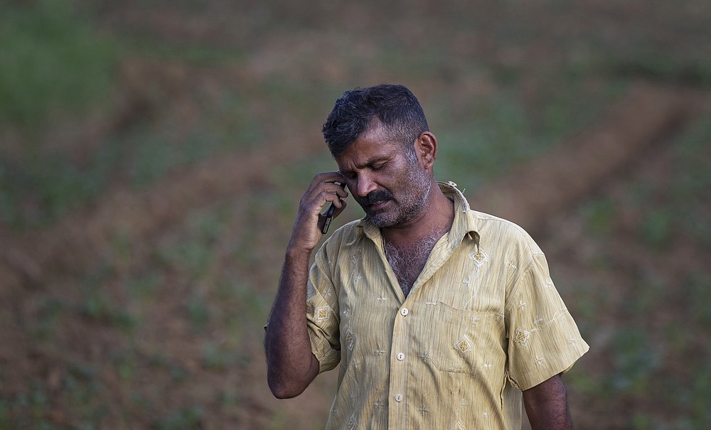 Sri Lankan potato farmer Pathmasiri Kumara speaks over his mobile phone as he checks the availability of fertilizer in the market in Keppetipola, Sri Lanka on July 1, 2021. Sri Lanka has cut back on imports of farm chemicals, cars and even its staple spice turmeric as its foreign exchange reserves dwindle, hindering its ability to repay a mountain of debt as the South Asian island nation struggles to recover from the pandemic. (AP Photo/Eranga Jayawardena)