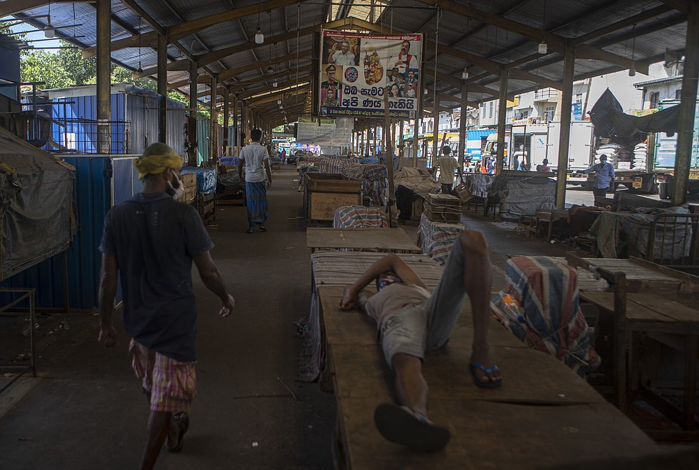 Workers rest at a wholesale market closed to curb the spread of the coronavirus in Colombo, Sri Lanka on  June 16, 2021. Sri Lanka has cut back on imports of farm chemicals, cars and even its staple spice turmeric as its foreign exchange reserves dwindle, hindering its ability to repay a mountain of debt as the South Asian island nation struggles to recover from the pandemic. (AP Photo/Eranga Jayawardena)