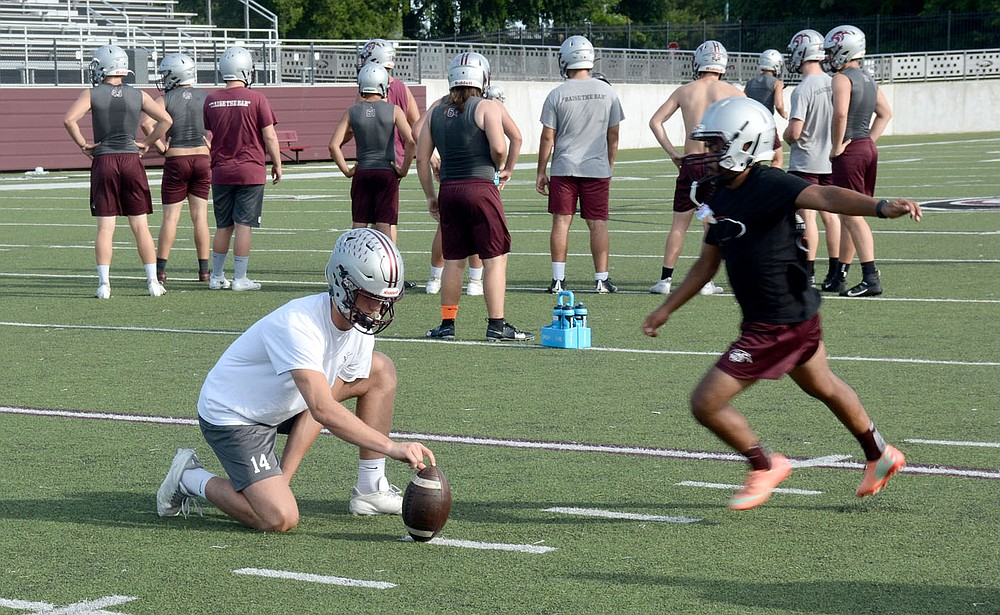 Graham Thomas/Siloam Sunday Siloam Springs quarterback Hunter Talley holds the ball as place kicker Ronald Mancia goes in for a field goal try during the Panthers' offseason workout Thursday morning at Panther Stadium.