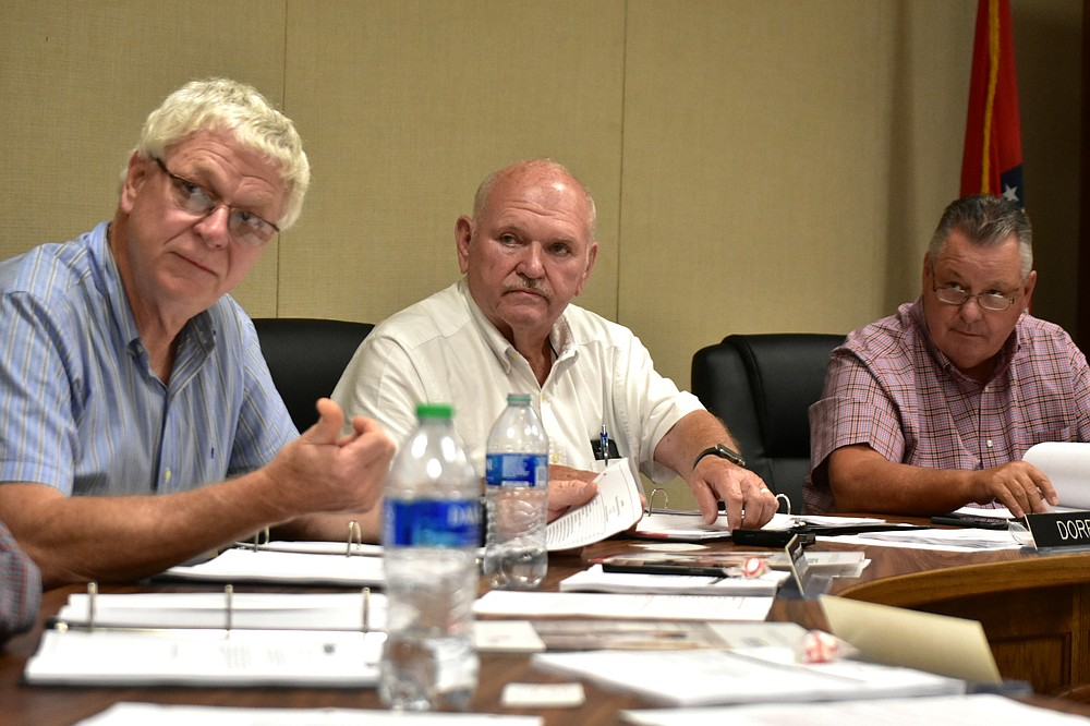 White Hall School District Superintendent Doug Dorris, center, listens to a question along with President Dr. Raymond Jones (left) and board member Scott Ray during a board meeting on Tuesday. (Pine Bluff Commercial/I.C. Murrell)