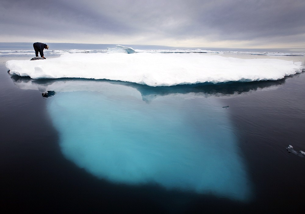 """FILE - In this file photo dated July 2007,  an Inuit seal hunter touches a dead seal atop an iceberg near Ammassalik Island, Greenland.  The left-leaning government on Greenland which could be sitting on vast amounts of oil, has decided to suspend all oil exploration, Friday July 16, 2021, calling it """"a natural step"""" because the Arctic government """"takes the climate crisis seriously."""" (AP Photo/John McConnico, FILE)"""